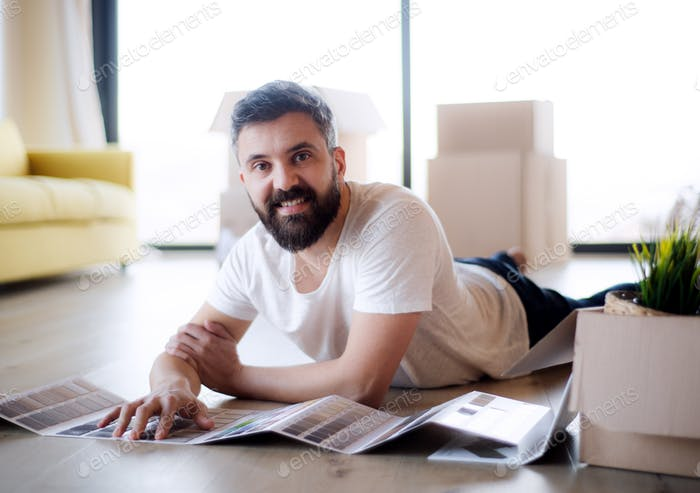 Mature man with boxes moving in new house, looking at color swatch.