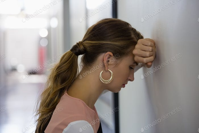Sad businesswoman leaning on wall