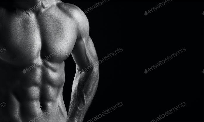 The torso of attractive male body builder on black background.