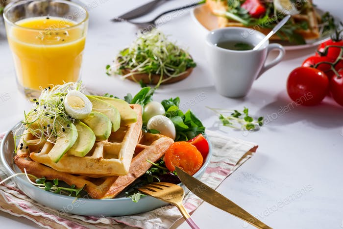 Belgian Waffles with avocado, eggs, micro green and tomatoes with orange juice on marble table