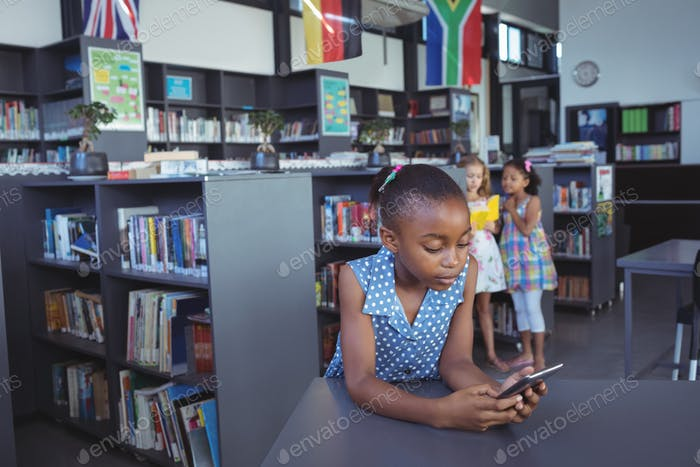 Girl using cellphone at desk in library