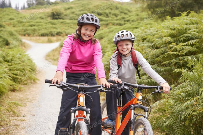 Two children sitting on their mountain bikes on a country path laughing, front view