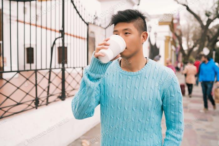 Asiatischer Mann trinkt eine Tasse Kaffee.