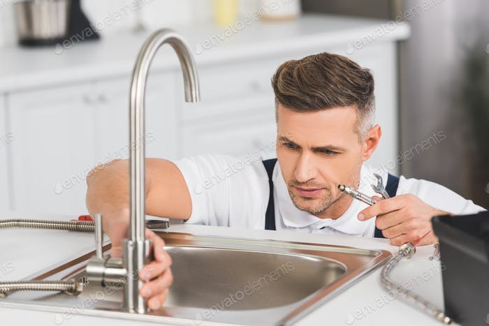 adult repairman holding pipe and spanner while repairing faucet at kitchen