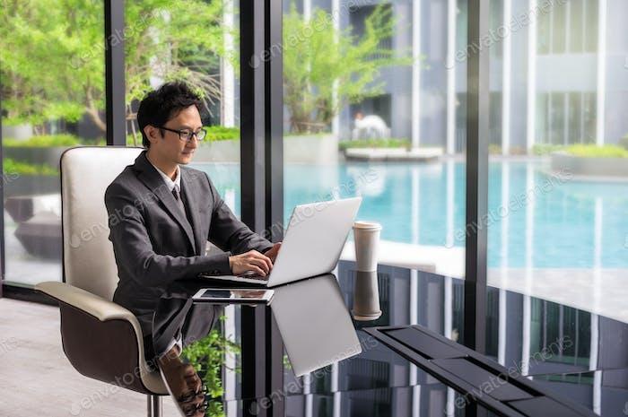 Glücklicher asiatischer Geschäftsmann, der auf dem Arbeitsraum sitzt und Laptop benutzt. Business Communication-Konzept