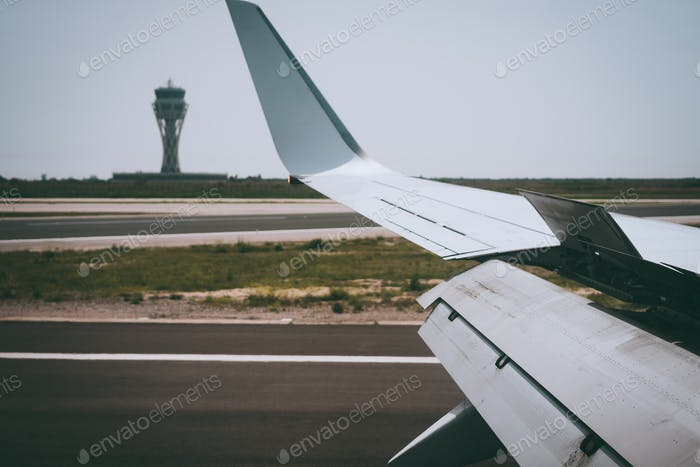 Wing of an aircraft open trailing edge flaps during landing. Airport Tower in background