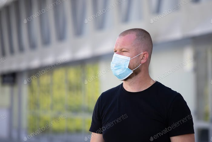 Portrait of brunette man in a medical surgical mask in the city.