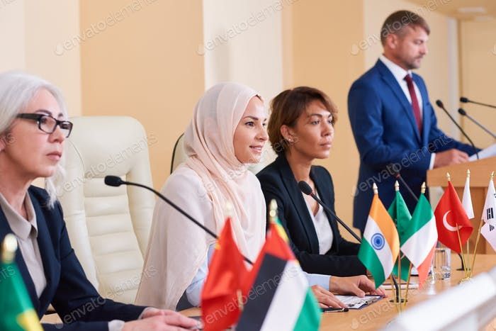 Pretty young muslim businesswoman listening to audience