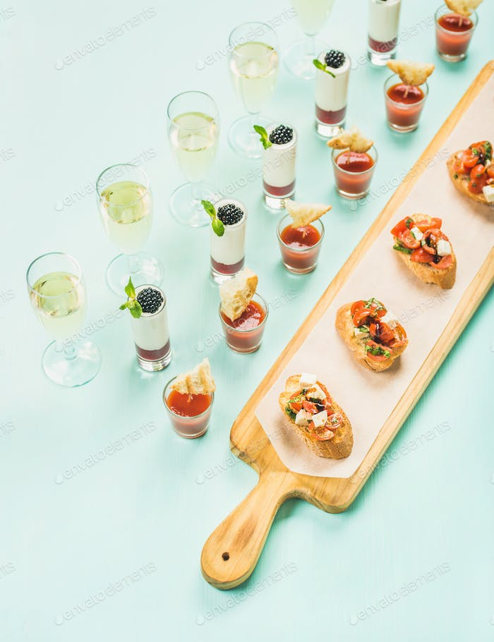 Snacks, brushettas, gazpacho shots, desserts, champagne over pastel blue background