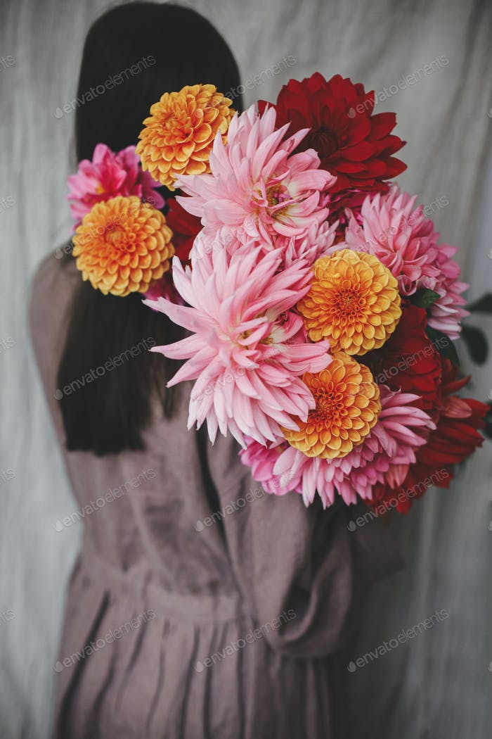 Beautiful woman holding autumn flowers bouquet in rustic room. Atmospheric aesthetic image