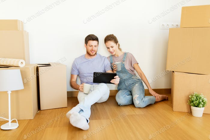 couple with boxes and tablet pc moving to new home