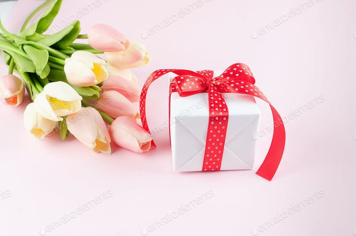 Gift box with bouquet of pink and white tulips on pink background. Spring or holiday concept