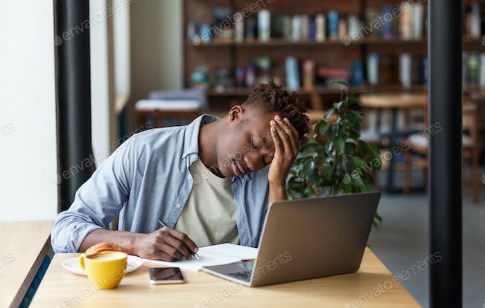 Exhausted black man studying online on laptop computer at cozy coffee shop