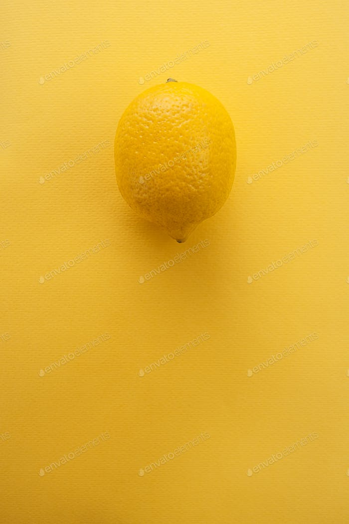 Fresh lemon on a bright yellow textured background with a place
