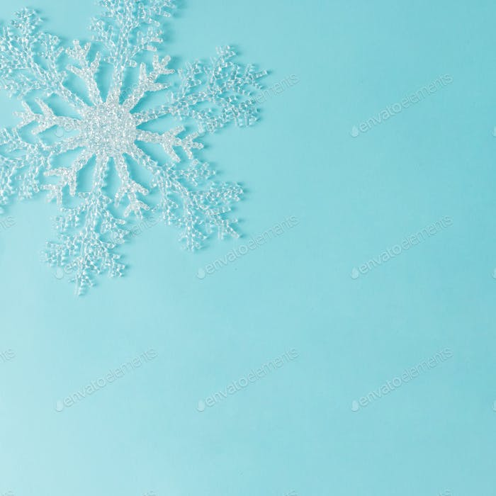 Minimal snowflake on bright blue background. Flat lay. Season concept.