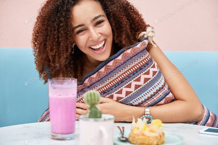 Cropped shot of joyful African American female being happy, meets with friend, eats cake and smoothi