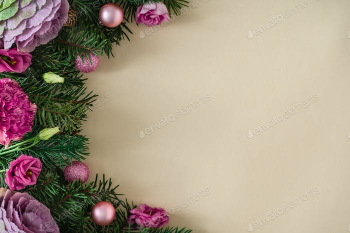 Natural Christmas composition with green pine tree branches, pink flowers and ball decoration.