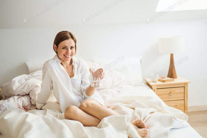 A young woman with night shirt sitting indoors on bed in the morning, holding water.