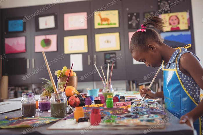 Side view of girl holding brush by color palettes on desk