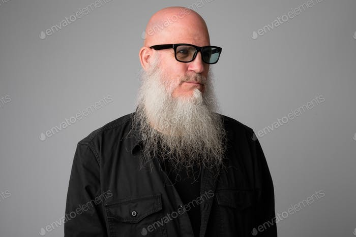 Face of mature handsome bald man with long beard thinking and wearing sunglasses