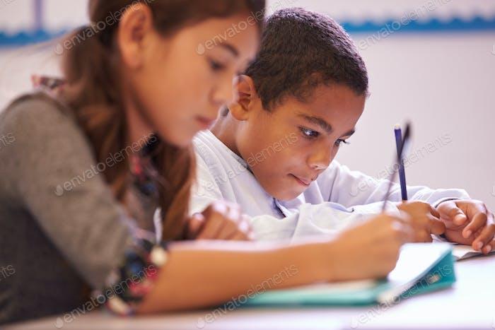 Zwei Grundschüler arbeiten während eines Unterrichts am Schreibtisch
