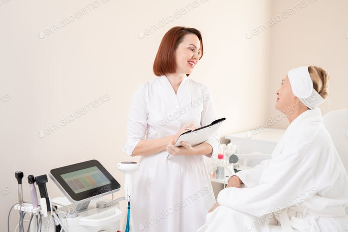 Friendly cosmetologist talking to client
