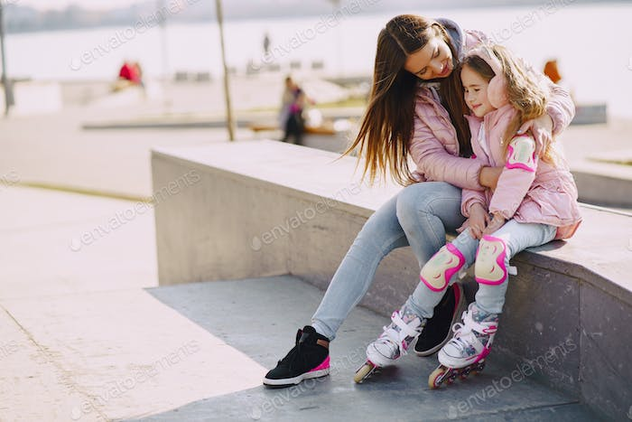 Mother with daughter in a spring park with roller