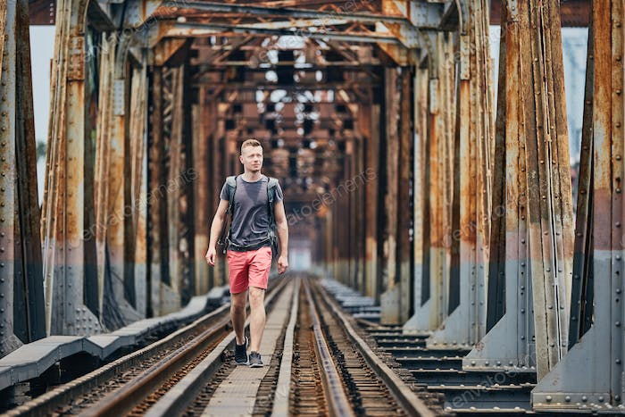 Traveler walking on railway bridge