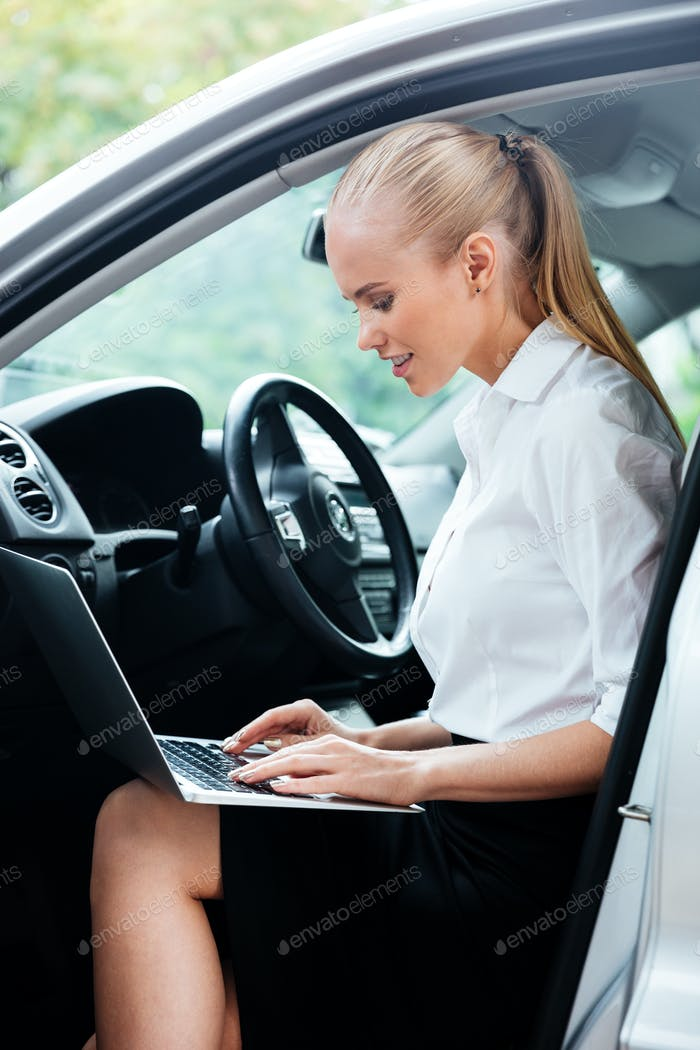 Businesswoman using laptop while sitting in car and working
