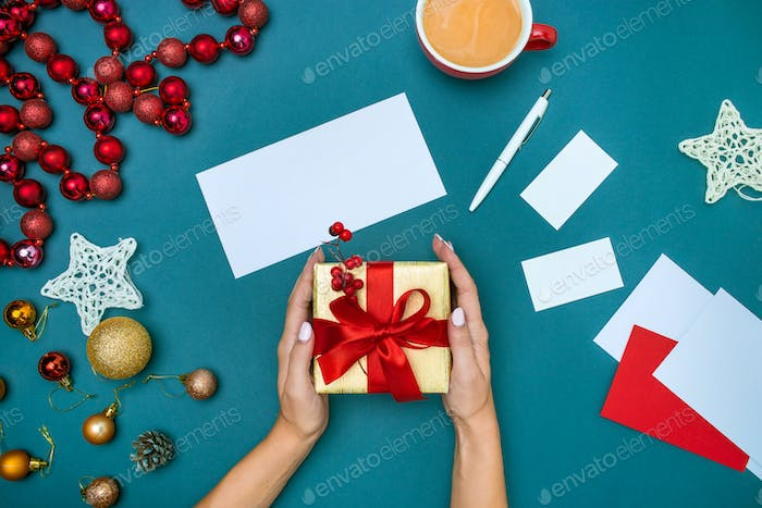 Hands of woman and Christmas gift box.
