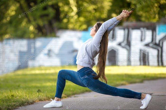 Schöne sportliche junge Frau in Yoga-Pose im Park