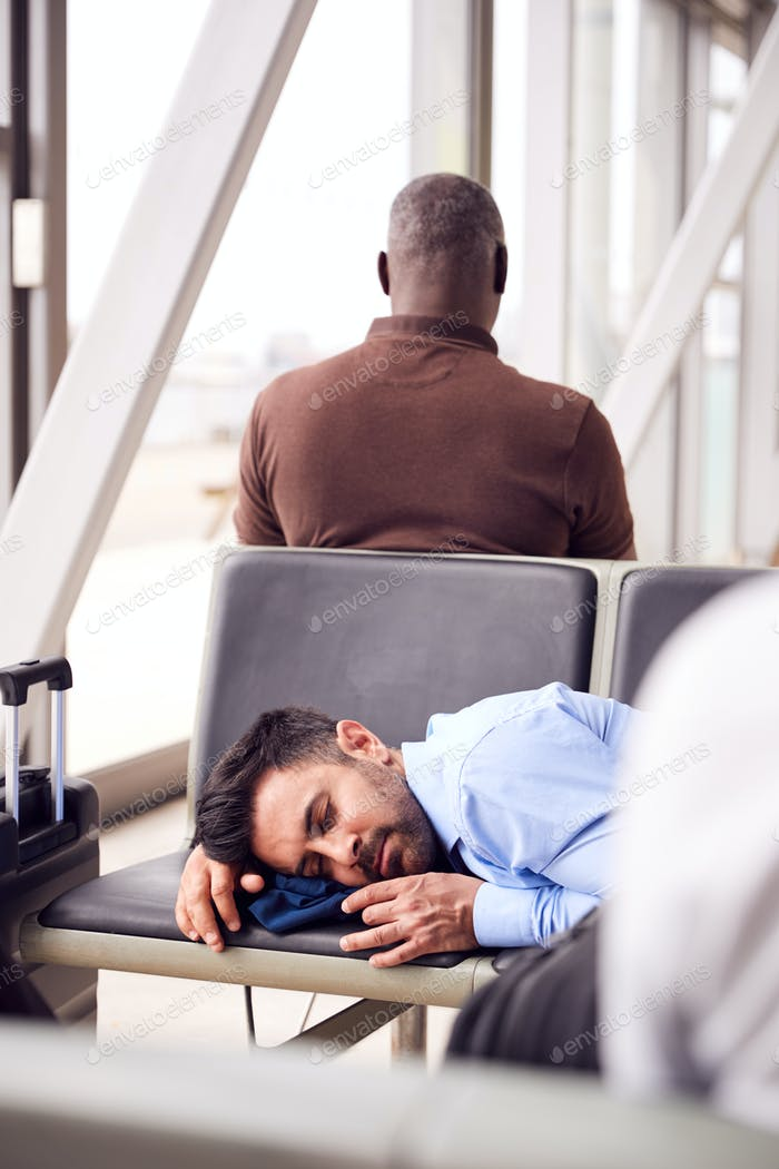 Businessman Sleeping On Seats In Airport Departure Lounge Because Of Delay