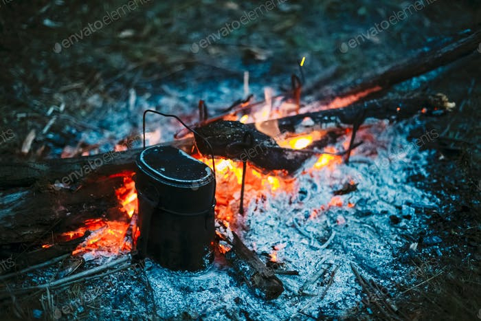 Food Is Cooked Over A Fire In An Old Vintage Retro Marching Pot