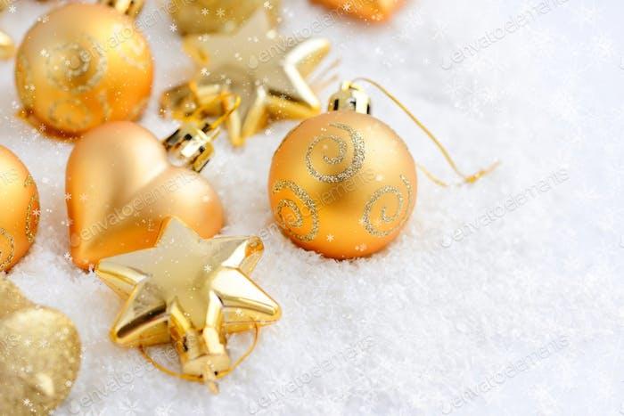 Weihnachtsgold-Ornamente auf dem Schnee. Festliche Weihnachten Backgrou