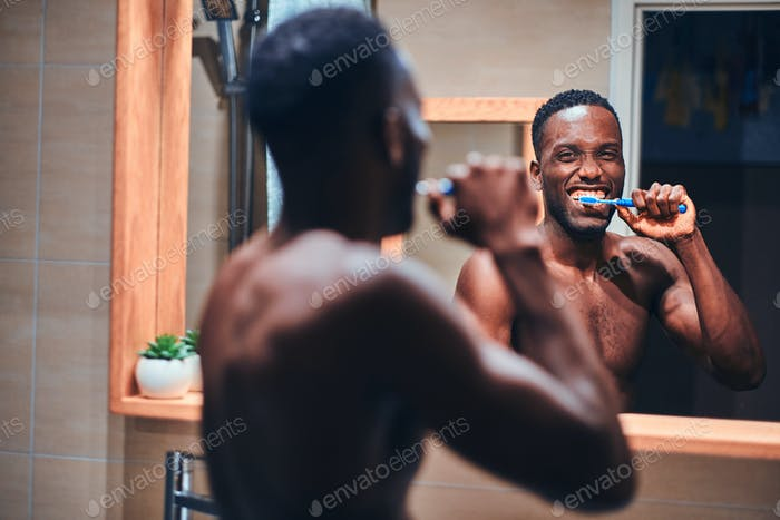 Concept of mourning routine - man is brushing his teeth
