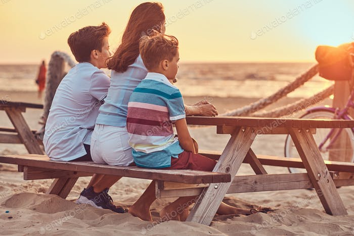 Mother with her sons sitting on a bench and looks at the bright sunset on the seacoast.