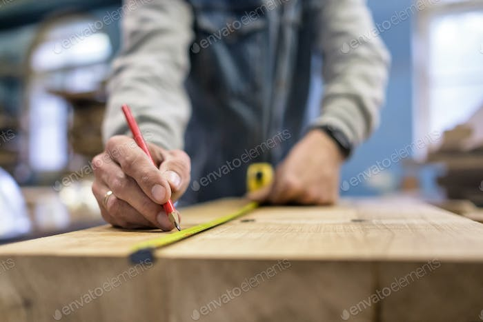 Carpenter measuring and tracing line with a ruler and pencil on wooden timber.