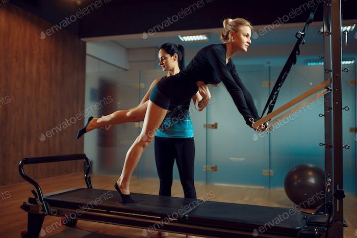 Schlanke Frau und Ausbilder, Pilates-Training