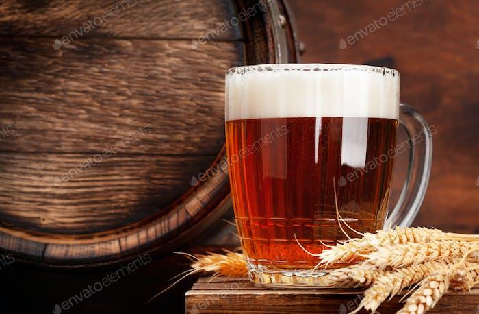 Mug of light lager beer and old wooden barrel