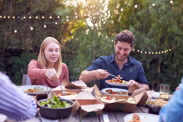 Friends In Garden At Home Sitting At Table Enjoying Food At Summer Garden Party