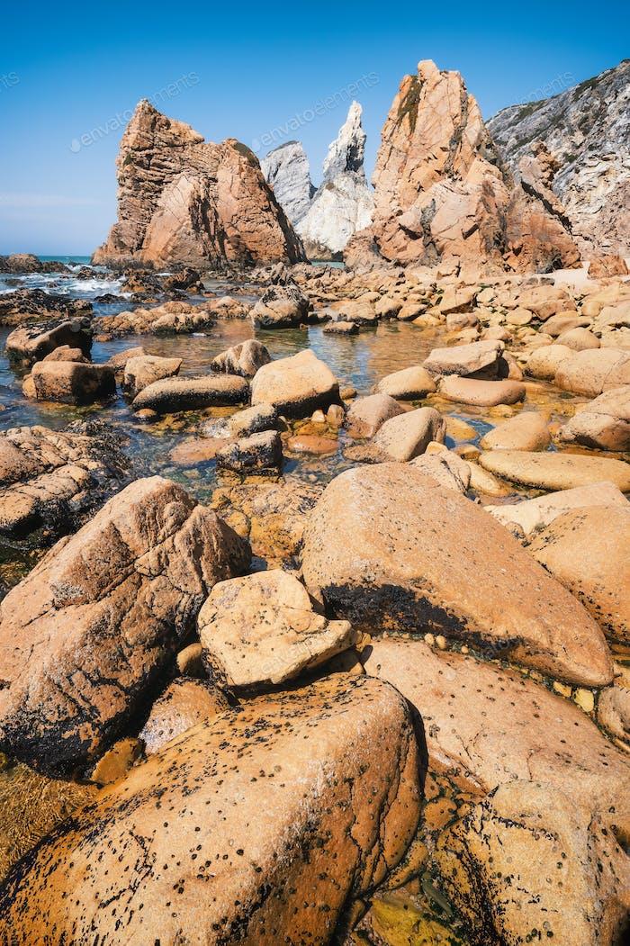 Rocky coastline of Praia Da Ursa beach, Sintra, Portugal. Giant sea stacks towering up from atlantic