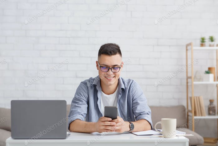 Modern hobby, gadgets and communication with followers remotely. Smiling guy in glasses typing on