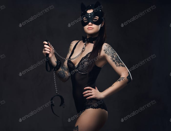 Sexy woman wearing black lingerie in BDSM cat leather mask and accessories posing on dark