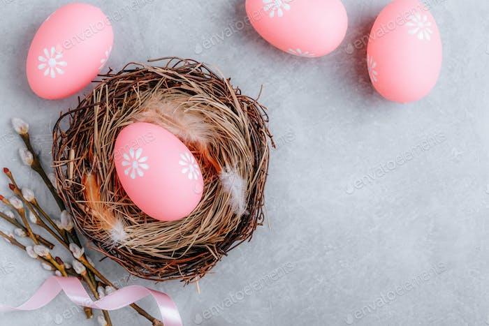 Buntes Osterei im Nest auf grauem Steinbetonhintergrund