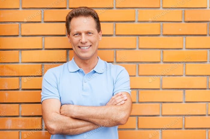 Happy house owner. Handsome mature man standing in front of a house holding arms crossed
