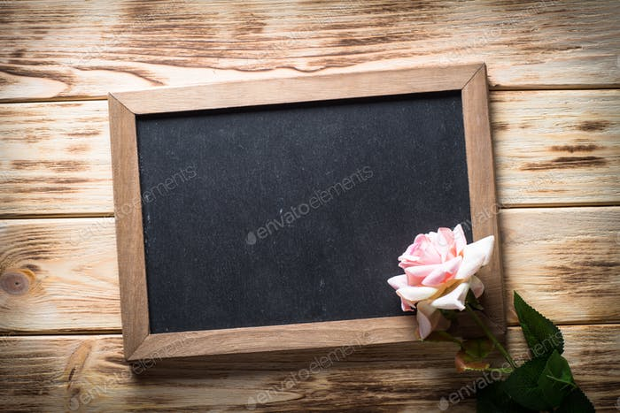 Chalckboard and rose flower on wooden table.