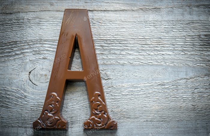 Chocolate letter on the wooden background