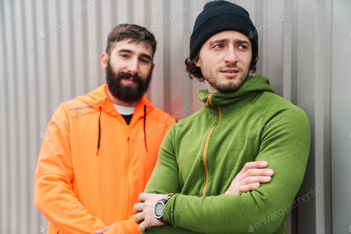 Zwei selbstbewusste junge Sportler ruhen nach dem Workout