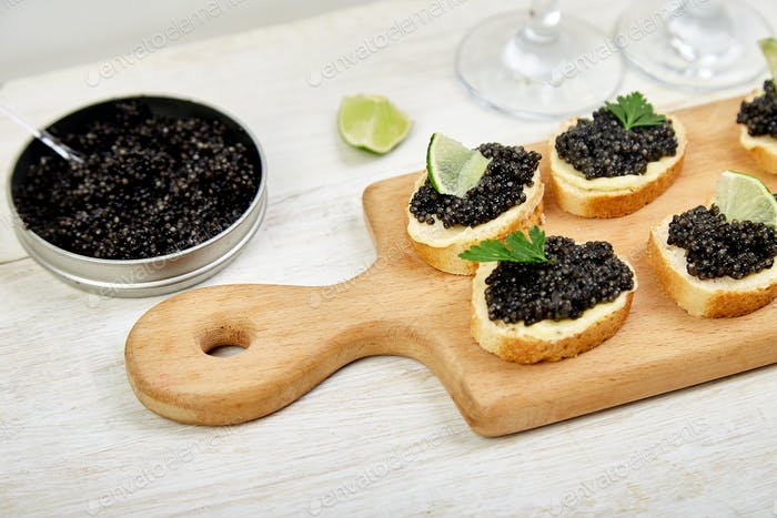 Sturgeon black caviar in wooden bowl, sandwiches and champagne on white background copy space.