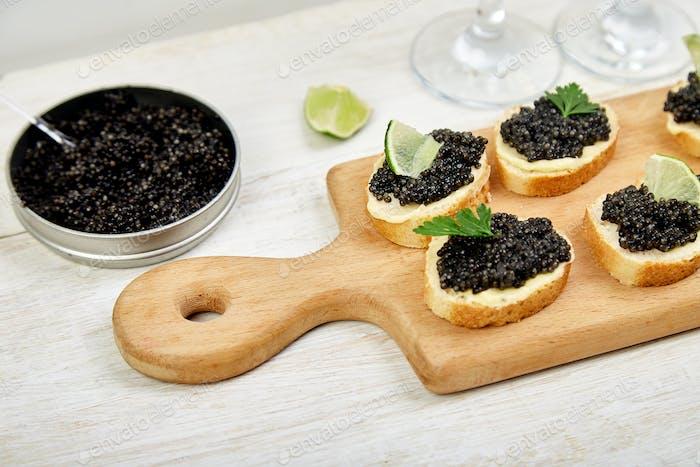 Stör schwarzer Kaviar in Holzschale, Sandwiches und Champagner auf weißem Hintergrund Kopie Raum.